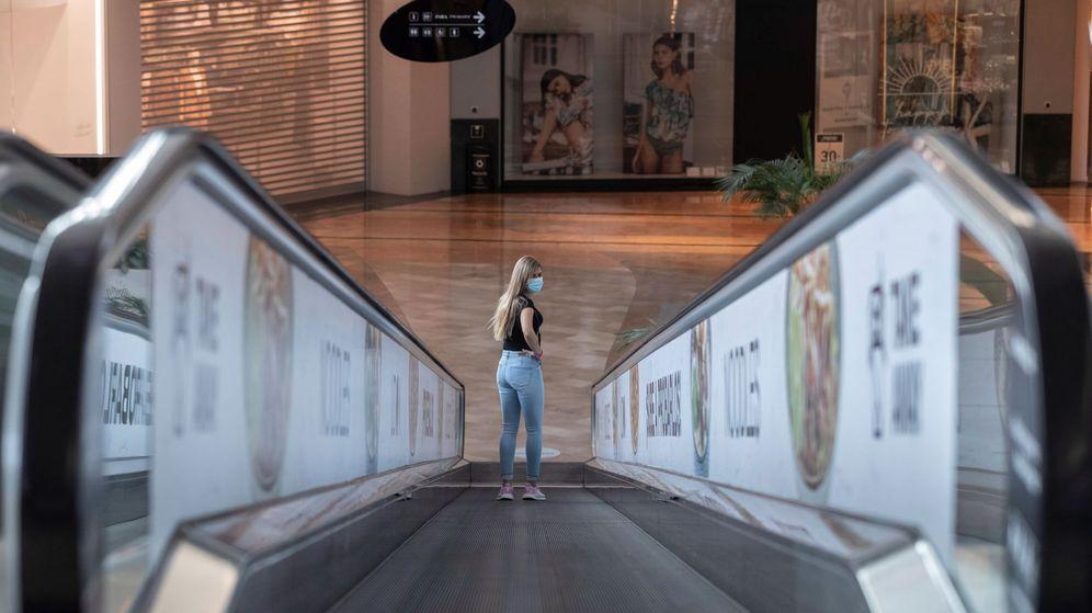 Foto: Una mujer con mascarilla en una escalera mecánica de un centro comercial de la Región de Murcia, casi al completo en la fase 2 de la desescalada. (EFE)