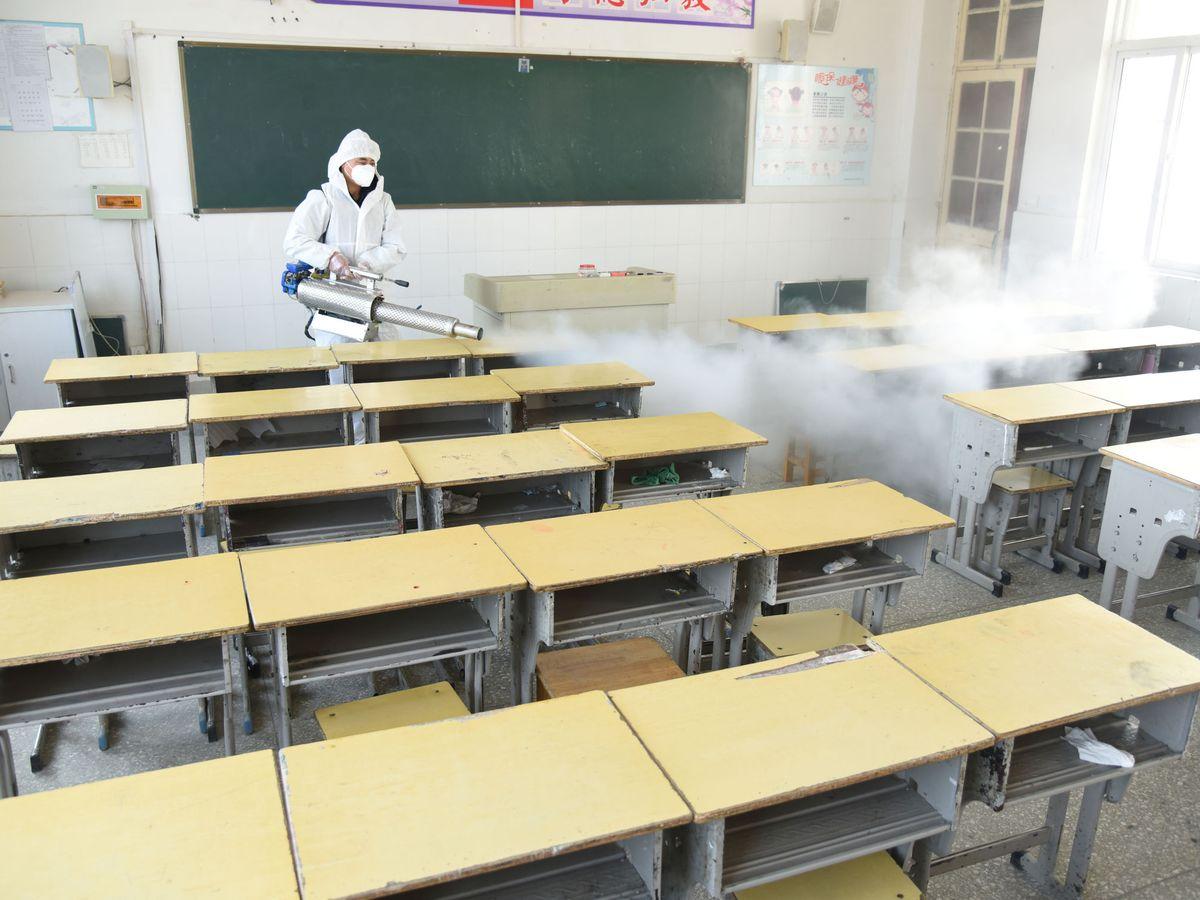 Foto: Un trabajador desinfecta una escuela primaria en China. (Reuters)