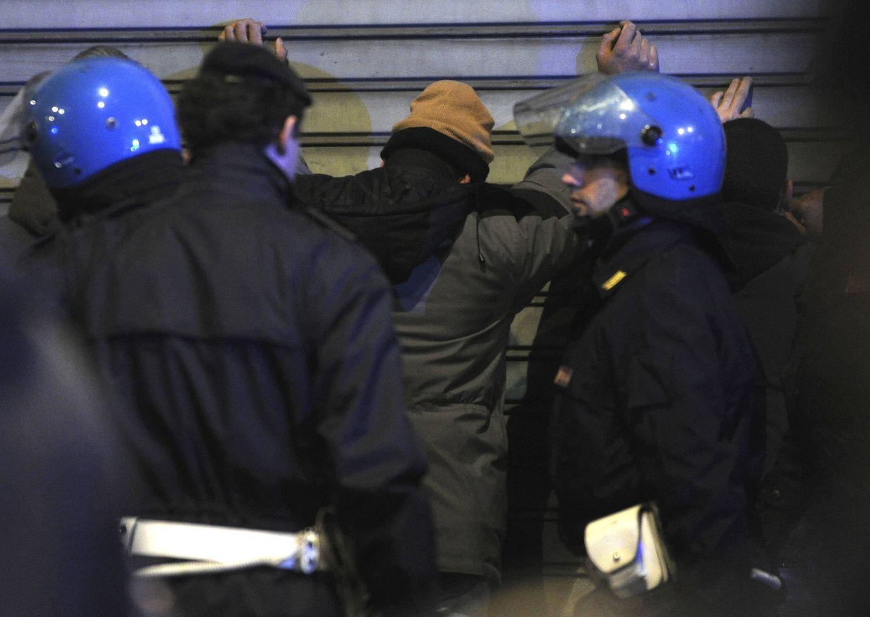 Foto: Policías italianos registran a sospechosos tras un pelea entre bandas latinas y africanas en el centro de Milán (Reuters).