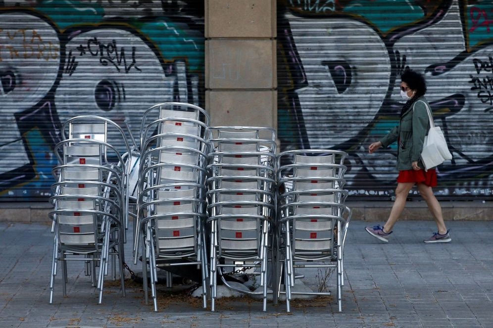 Foto: Una mujer pasa con mascarilla delante de un restaurante cerrado en la Rambla de Cataluña, en Barcelona, este 18 de mayo. (EFE)