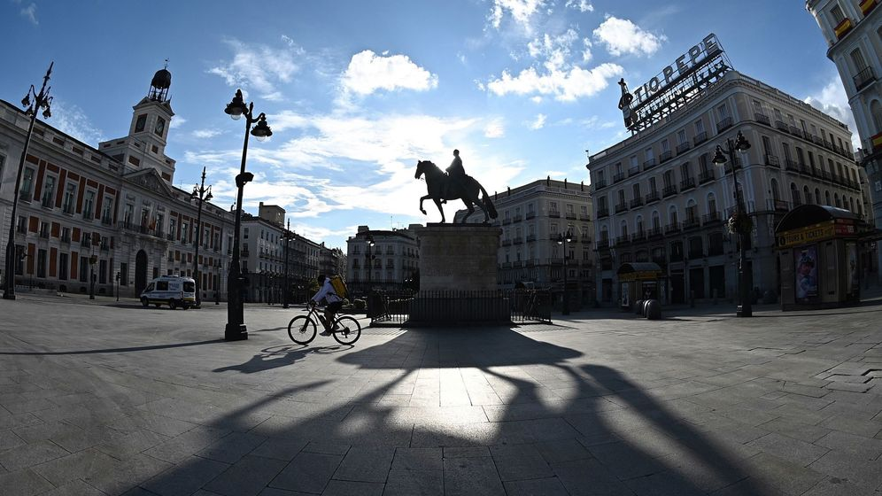 Foto: Un repartidor cruza en bicicleta la Puerta del Sol, en Madrid. (EFE)