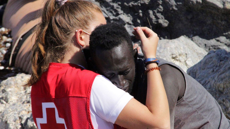 Una trabajadora de Cruz Roja abraza a un migrante que ha logrado llegar a Ceuta (EFE)
