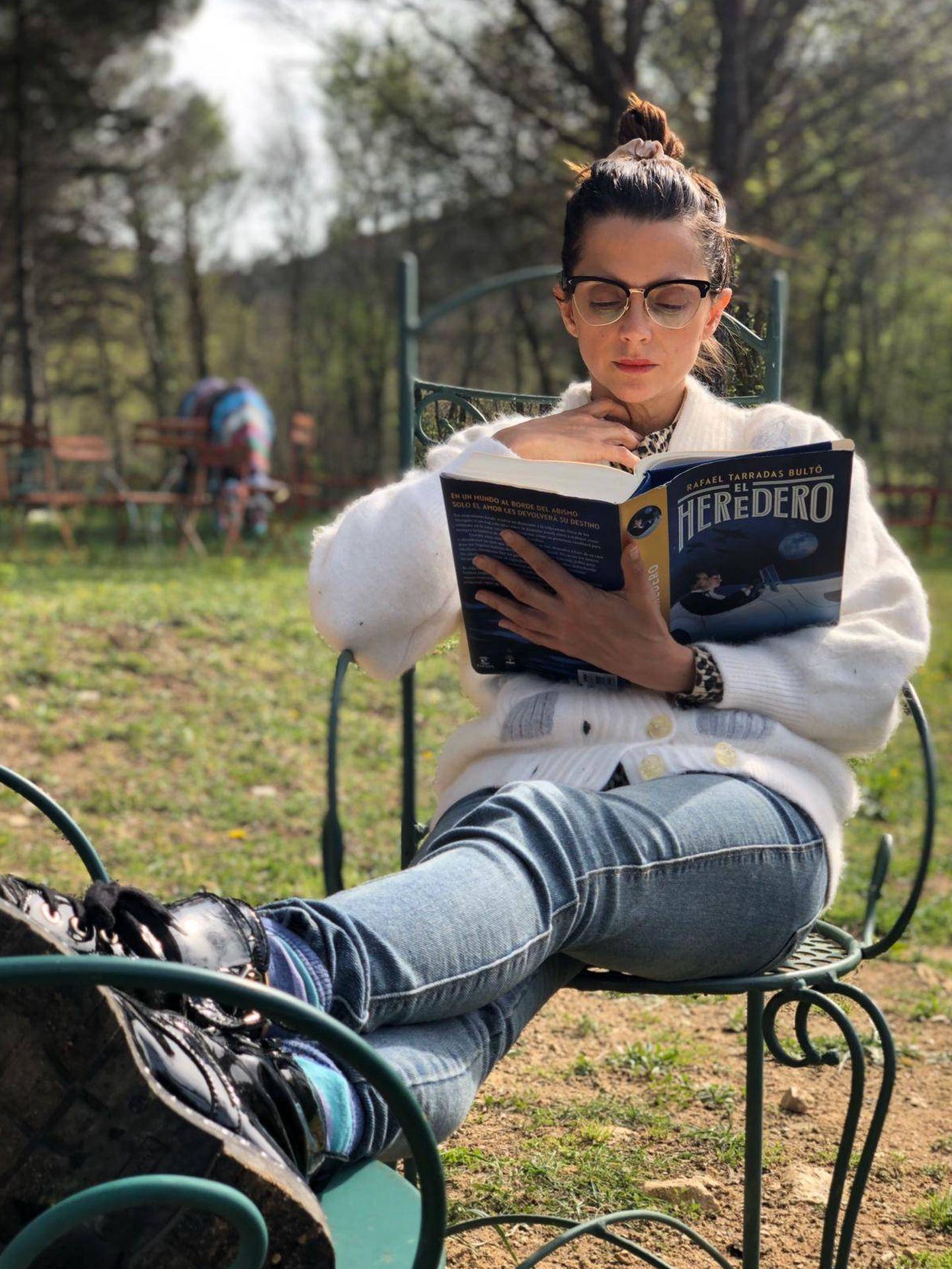Macarena Gómez lee 'El heredero' con un cerdo al fondo.