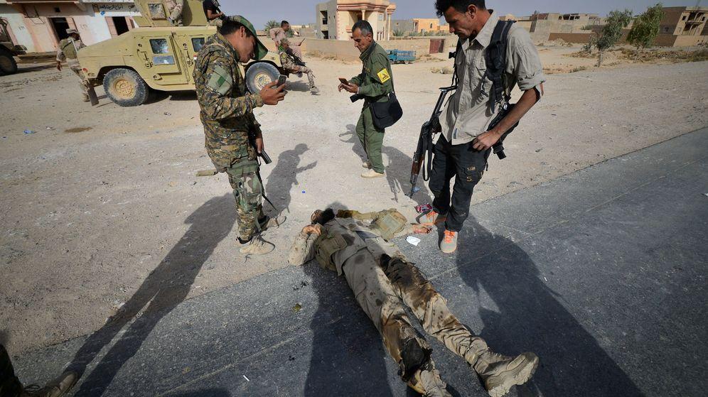 Foto: Miembros de una milicia chií observan el cadáver de un militante del ISIS tras la liberación de la ciudad de Al Qaim, en noviembre de 2017. (Reuters)