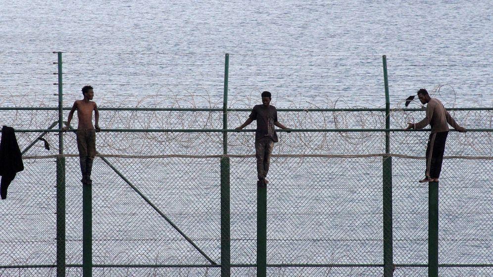 Foto: Más de un centenar de inmigrantes tras saltar la valla fronteriza con Ceuta (EFE).