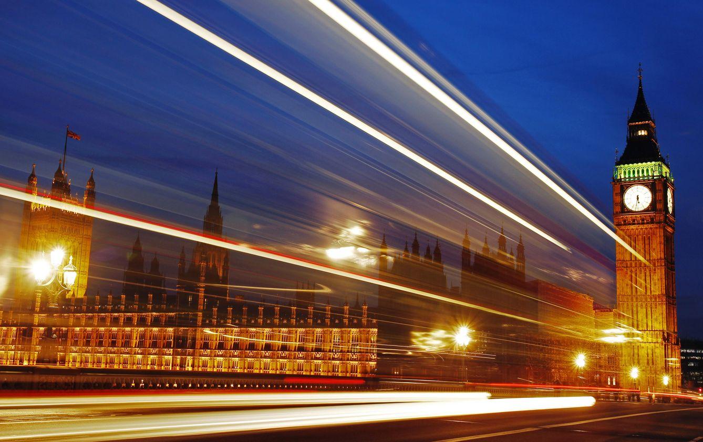 Foto: Las luces de un autobús que pasa al caer la noche ante el Parlamento británico, en Londres. (Reuters)