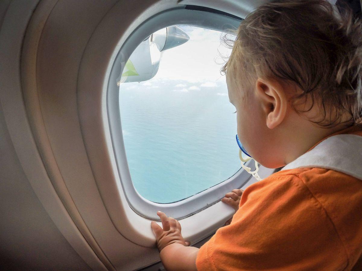 Foto: Un bebé se asoma a la ventanilla de un avión. (iStock)