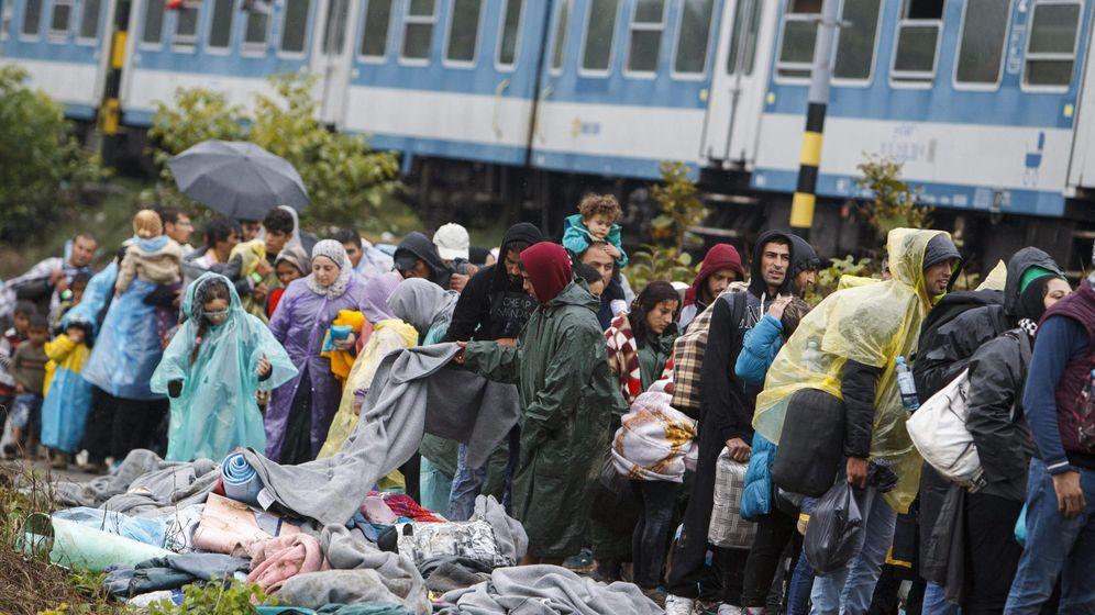 Foto: Los refugiados en un control de acceso al tren esperan en la frontera entre Croacia y Hungría. (EFE)