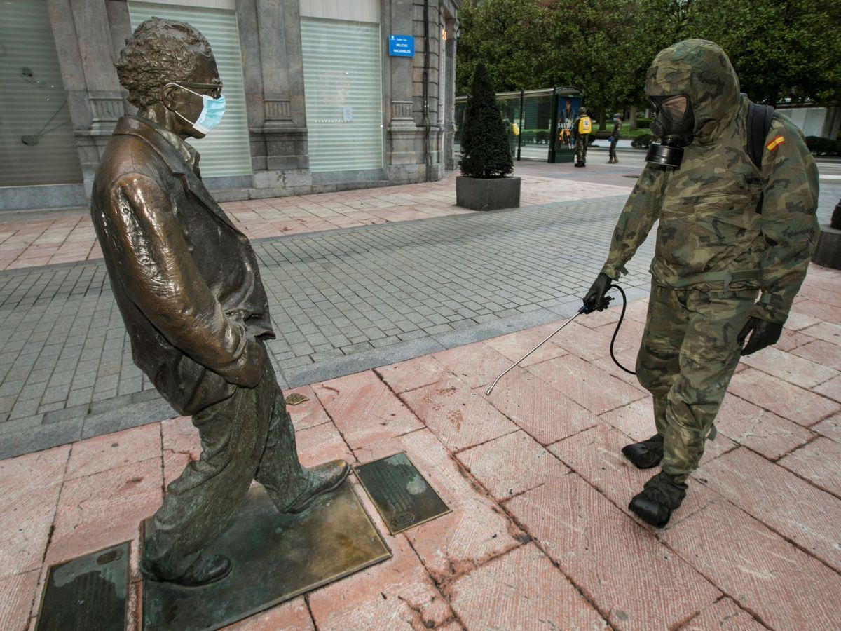 Foto: Un soldado desinfecta la estatua de Woody Allen, con mascarilla, en Oviedo. (EFE)