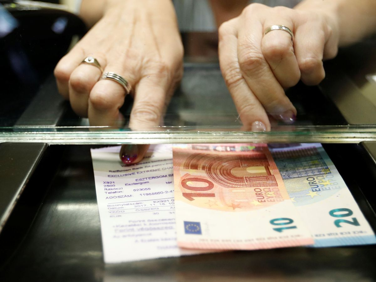 Foto: Una mujer ingresa billetes de euros en una tienda de cambio de divisas. (Reuters)