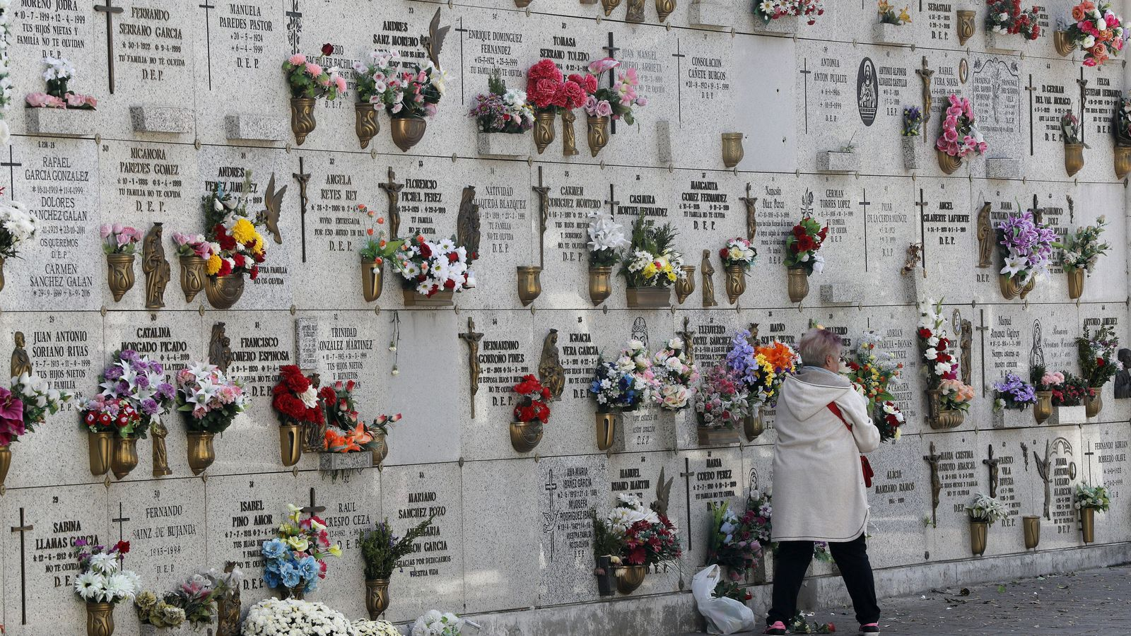 Foto: Una mujer pasa junto a una pared de columbarios en el cementerio de La Almudena de Madrid. (EFE)