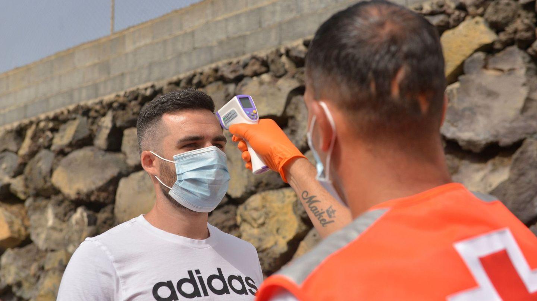Un operario de la Cruz Roja toma la temperatura a un asistente a un partido de fútbol. (EFE)