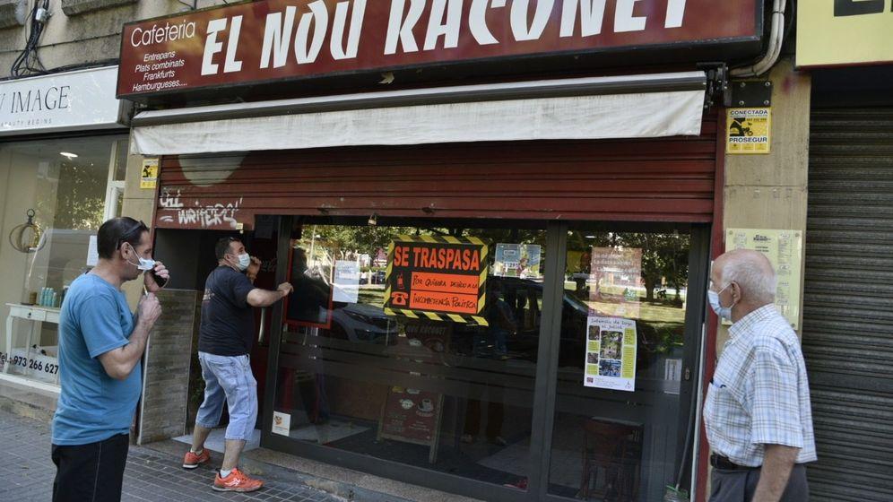 Foto: Un hombre en Lleida cierra su bar, que luce un cartel de traspaso. (EFE)