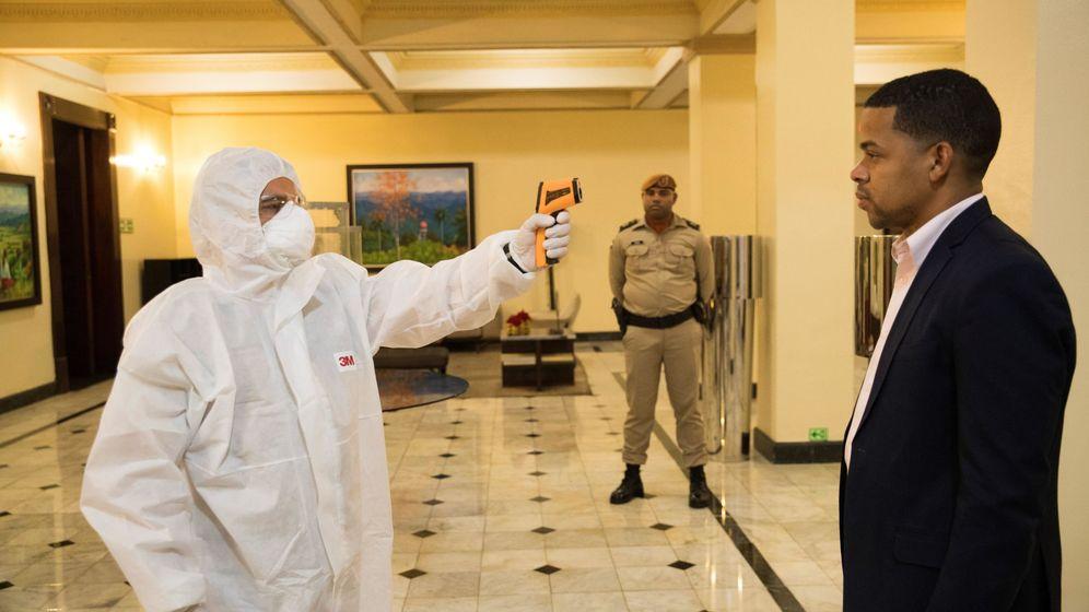 Foto: Personal de salud toma la temperatura a personas que ingresan al Palacio Nacional, este sábado, en Santo Domingo. Foto: Efe