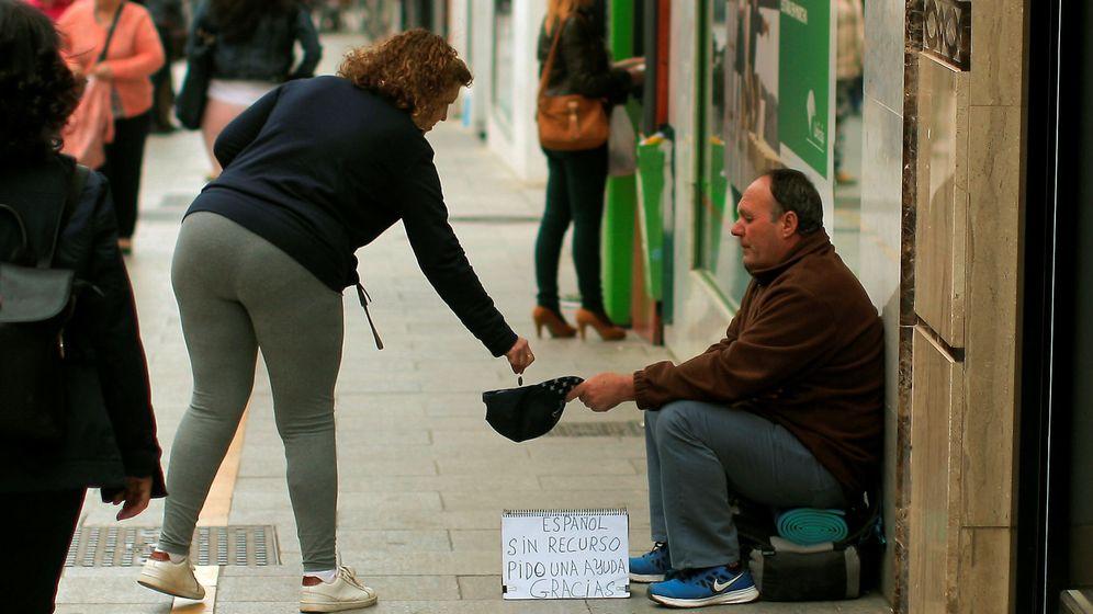 Foto: Una mujer da limosna a un mendigo en Ronda. (Reuters)