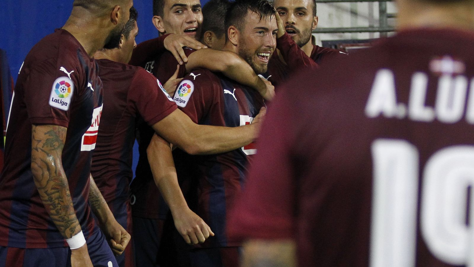 Foto: Enrich, abrazado por sus compañeros tras marcar y Luna, acercándose a ellos (Javier Etxezarreta/EFE).