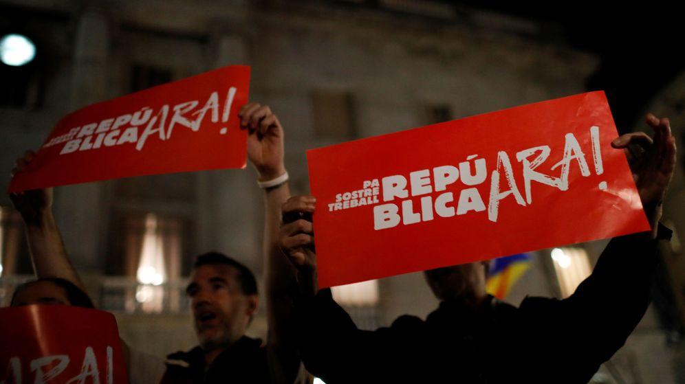 Foto: Manifestantes con pancartas donde se lee 'República ahora', en la plaza Sant Jaume de Barcelona. (Reuters)