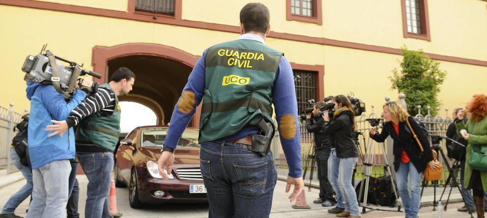 Foto: Agentes de la UCO de la Guardia Civil protegen la salida de un vehículo en la sede de la Diputación Provincial de Sevilla. (EFE)