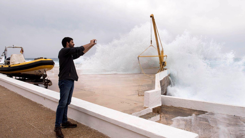 Un hombre fotografía el oleaje en el paseo marítimo de la urbanización S'Algar, en el municipio de Sant Lluís (Menorca). (EFE)
