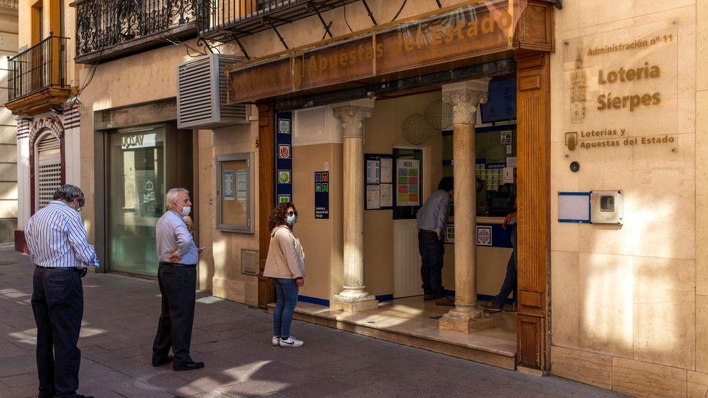 Foto:  Varias personas hacen cola en la puerta de una administración de Loterías en la calle Sierpes de Sevilla. (EFE)