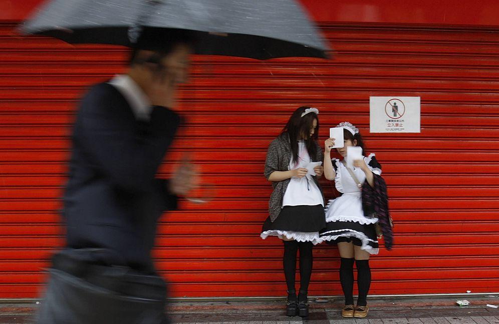 Foto: Un hombre pasa ante dos jóvenes japonesas disfrazadas en el centro de Tokio (Reuters).