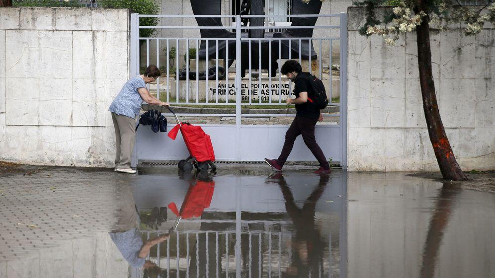Foto: Dos personas intentan pasar por una zona inundada en la avenida de Pío XII, en Madrid, a causa de las fuertes lluvias y el granizo. (EFE)