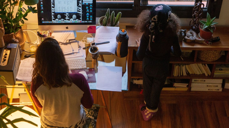 Una mujer realiza teletrabajo en su casa mientras su hija juega a su lado. (EFE)