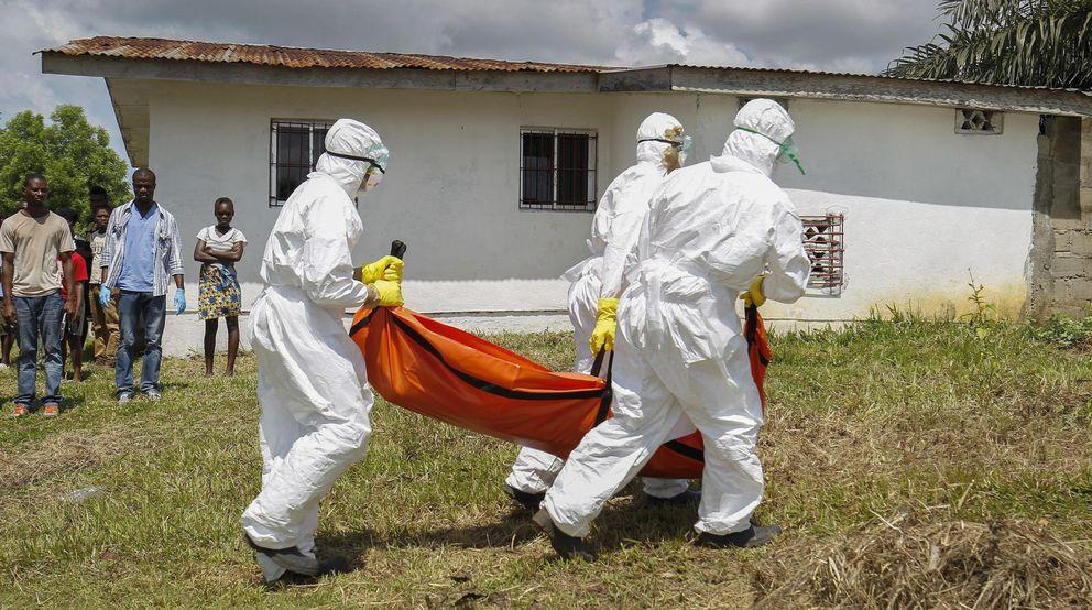 Foto: Voluntarios de Cruz Roja transportan equipos con trajes aislantes a un fallecido por el virus del Ébola en Libera (Efe)