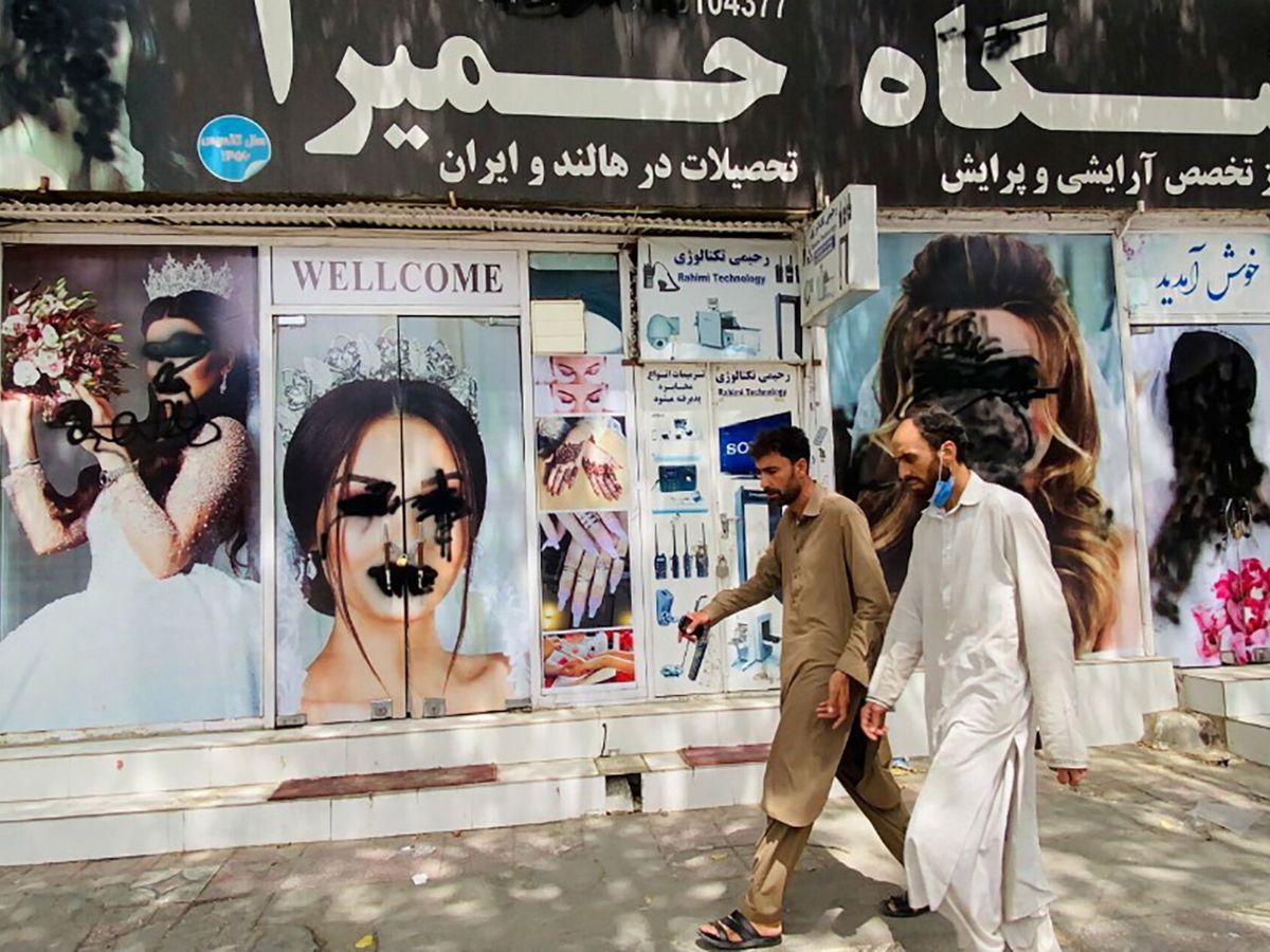 Foto: Dos hombres pasan ante un salón de belleza en Kabul. (EFE)