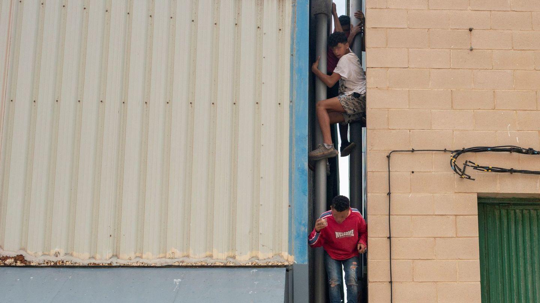 GRAF3474. CEUTA, 21 05 2021.- Tres migrantes se escapan de la nave del polígono industrial cercano a la playa de El Tarajal en donde permanecen gran parte de los menores migrantes llegados a Ceuta. La frontera del Tarajal que separa Ceuta de Marruecos así como el espigón fronterizo no han registrado esta noche ni a primeras horas de la mañana de este viernes intentos de entrada, de modo que no se cumplen ya dos días sin actividad en la zona. EFE  Brais Lorenzo