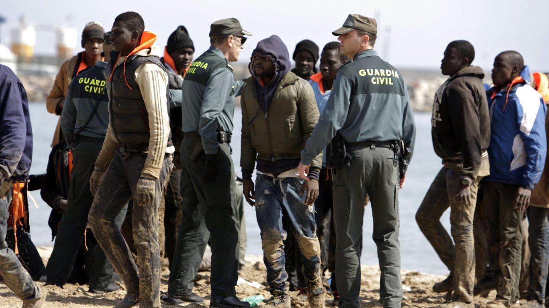 Varios miembros de la Guardia Civil junto a un grupo de inmigrantes. (EFE)