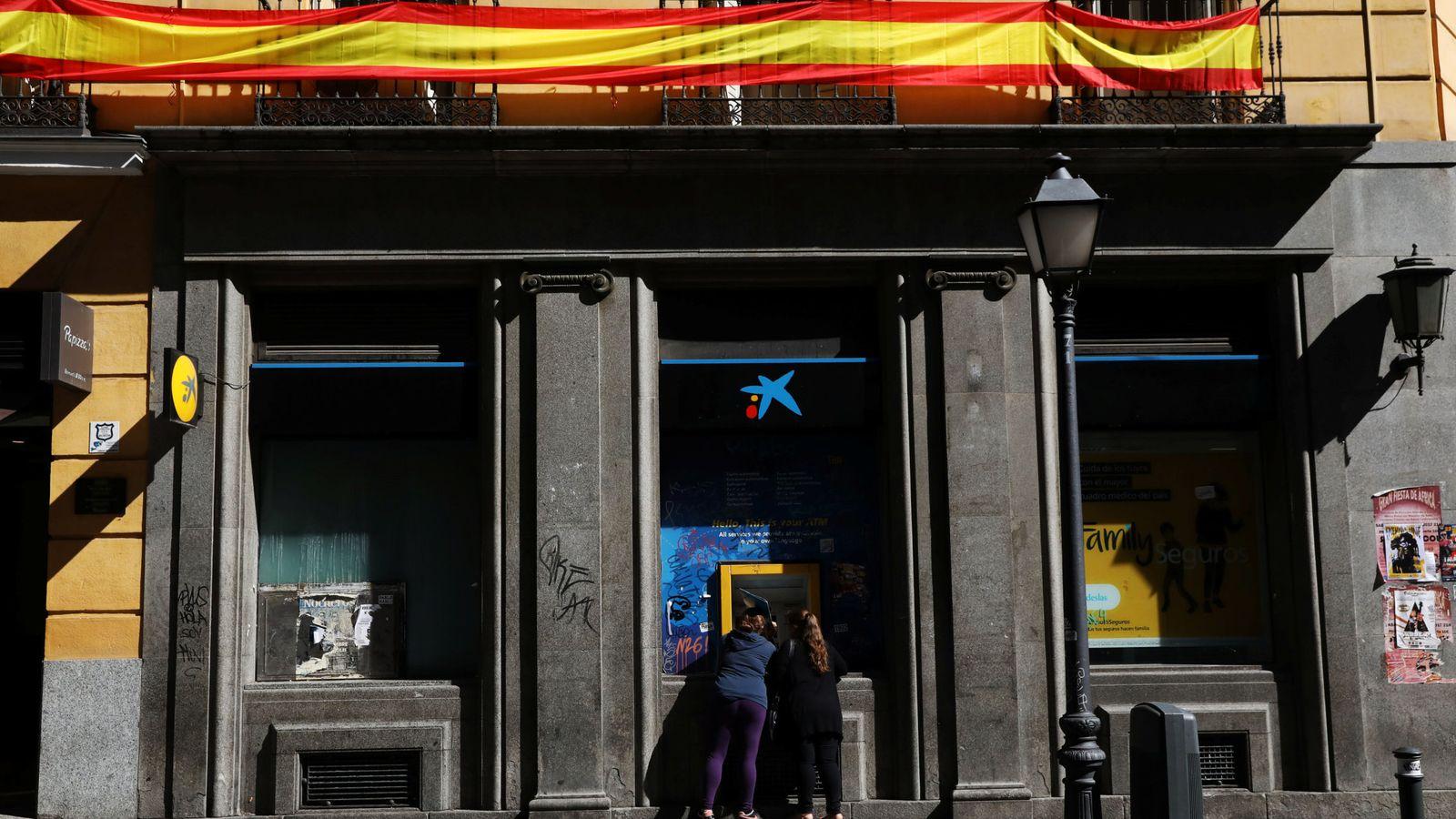 Foto: Un cajero de CaixaBank bajo una bandera española en Madrid. (Reuters)