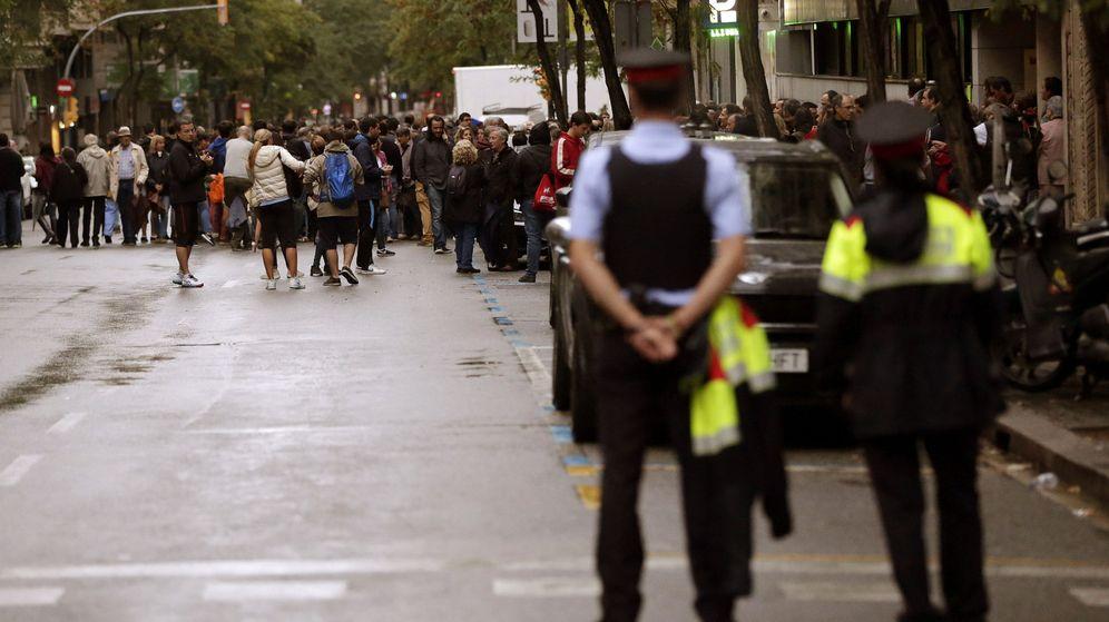 Foto: Dos 'mossos' observan a la gente congregada ante el colegio Infant Jesús de Barcelona durante la jornada del 1-O. (EFE)