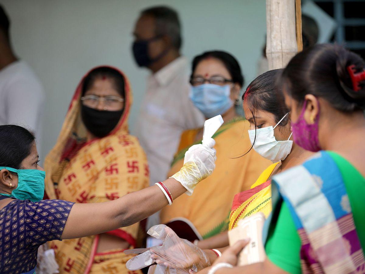 Foto: Una sanitaria toma la temperatura en India. (EFE)