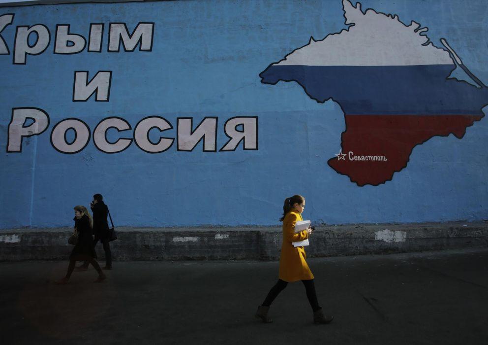 Foto: Una mujer pasa ante un mural que muestra el mapa de Crimea adornado con los colores de la bandera rusa en Moscú. (Reuters)