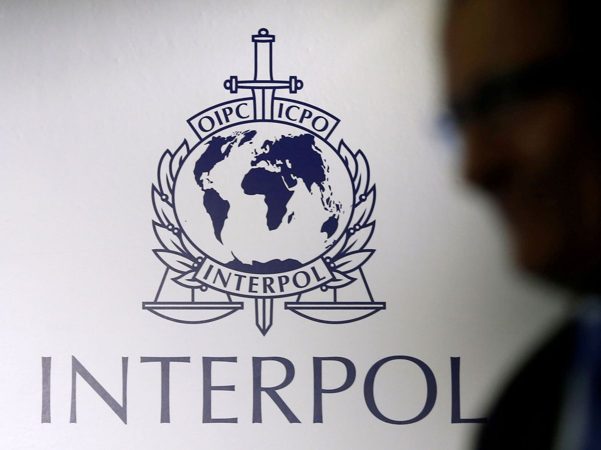 Foto: Un hombre pasa junto a un logotipo de Interpol. (Reuters)