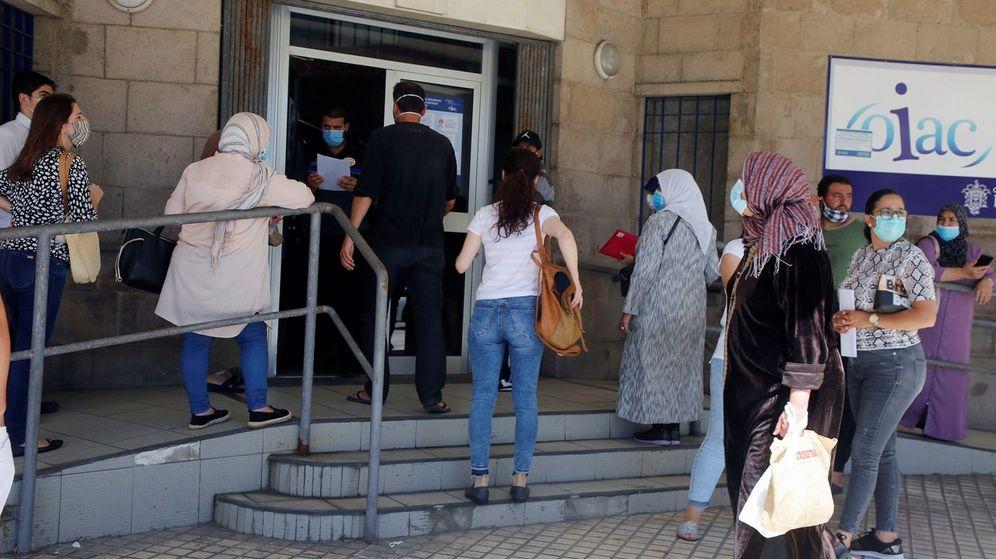 Foto: Varias personas esperan su turno para solicitar los documentos con los que pedir el ingreso mínimo vital. (EFE)