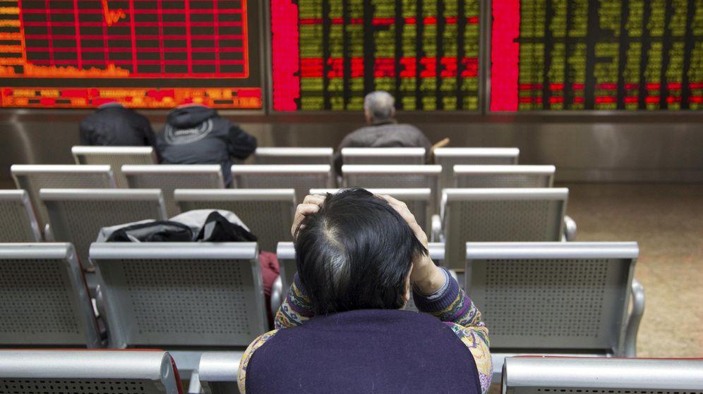 Foto: Un inversor delante de una pantalla con información bursátil en Pekín. (Reuters)
