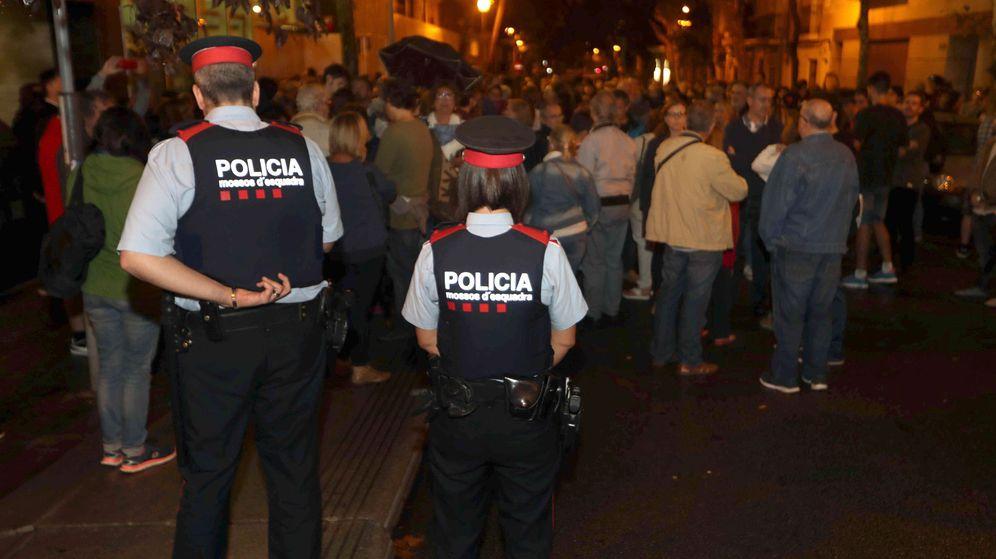 Foto: Dos Mossos custodian la puerta de un colegio en el barrio de Sants de Barcelona, en el que una multitud esperaba para votar. (EFE)