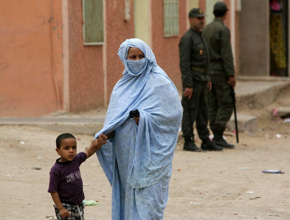 Foto: Una madre saharaui y su hijo pasan delante de dos policías marroquíes en El Aaiun, en 2005 (Reuters)