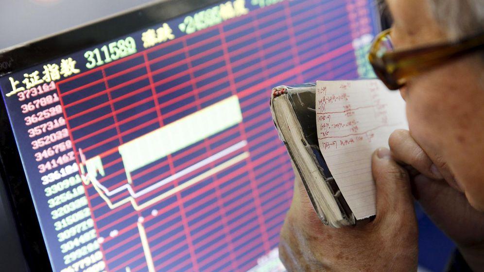 Foto: Un inversor mira uno de los paneles de la bolsa china. (EFE)