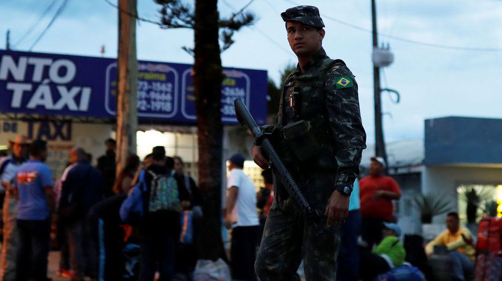 Foto: Un soldado patrulla una calle llena de inmigrantes venezolanos que acaban de cruzar el puesto fronterizo de Pacaraima, Brasil, el 19 de agosto de 2018. (Reuters)