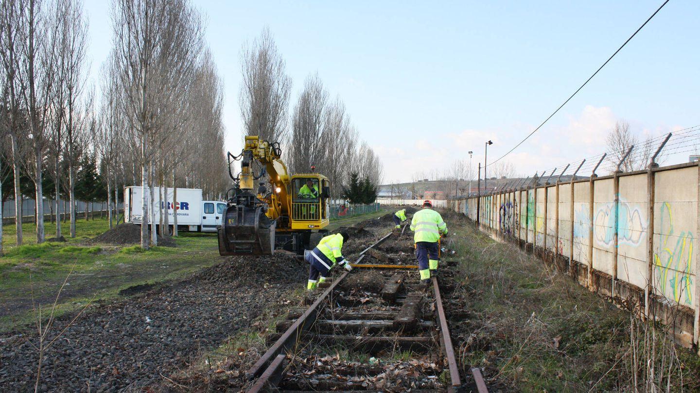 Los obreros levantan la antigua vía del tren hacia la papelera. (R. M.)