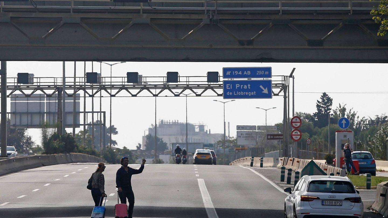 Dos viajeros tratan de llegar al aeropuerto de El Prat, bloqueado por los manifestantes. (EFE)