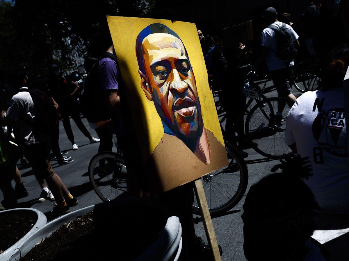 Foto: Una persona sostiene una pancarta con un retrato de George Floyd durante las protestas contra el racismo en Nueva York. (Reuters)