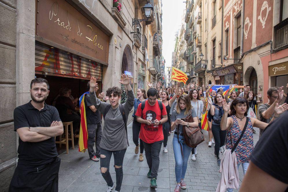 Foto: Manifestantes marchan frente a una cafetería a medio cerrar con clientes dentro. (David Brunat)