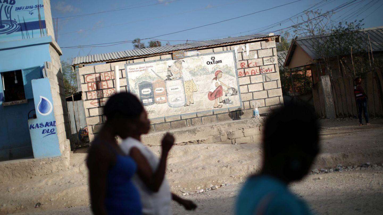 Mujeres pasan junto a un cartel de Oxfam en Corail, un campo de desplazados del terremoto de 2010, en las afueras de Puerto Príncipe (Reuters)