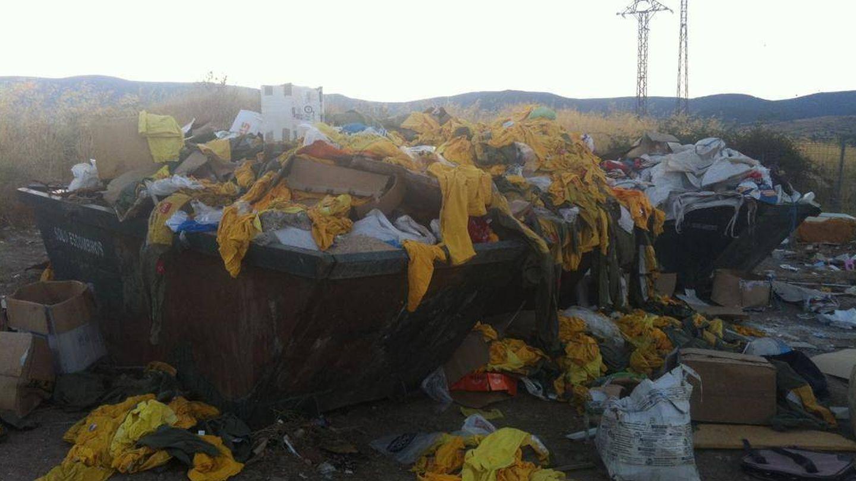 Trajes de los bomberos tirados a un contenedor de basura.