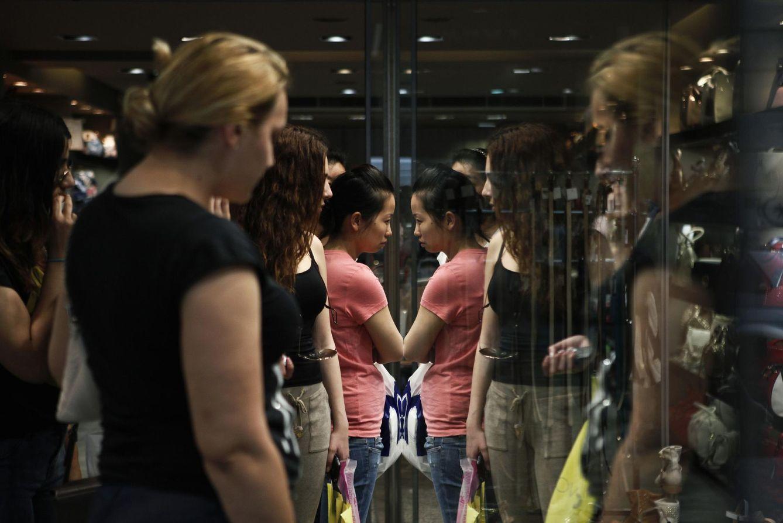 Foto: Mujeres reflejadas en el escaparate de una tienda en el centro comercial Ermou Street, en el centro de Atenas (Reuters).