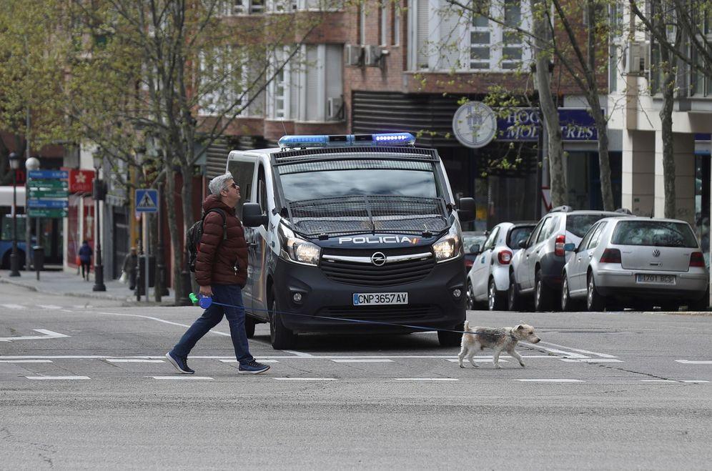 Foto: Un hombre pasea a su perro ante un furgón de la Policía Nacional durante el estado de alarma. (EFE)